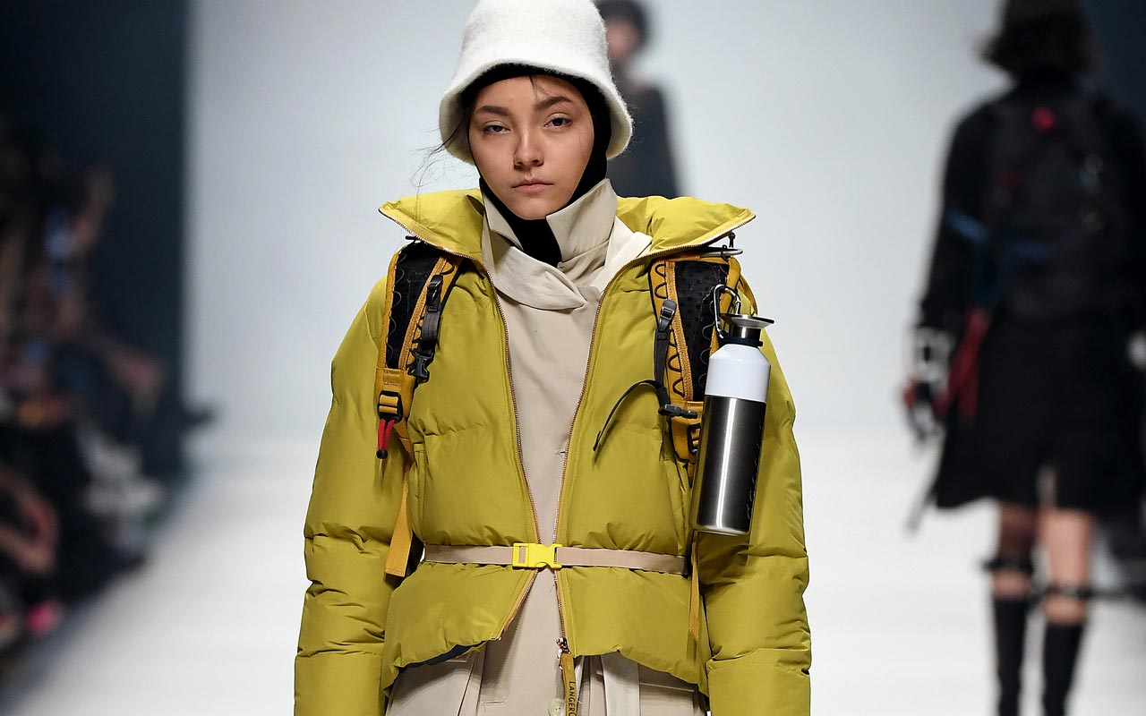Jacket: LANGER CHEN, Coat & Belt: PEOPLE BERLIN, Hood: FALKE, Hat: SANDERMANN, Socks: SWEDISH STOCKINGS, Backpack: KLÄTTERMUSEN, Water bottle: DOPPER Shoes VEJA (Foto: Alexander Koerner Gerry Images for MBFW)